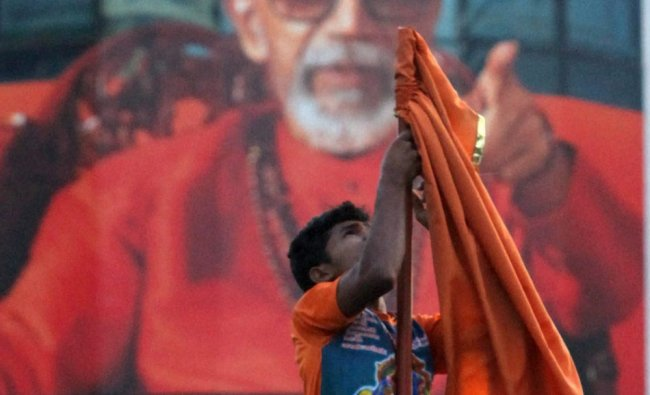 Shiv Sena worker removes the party flag from the Sena Bhavan after the news of Thackeray\'s death