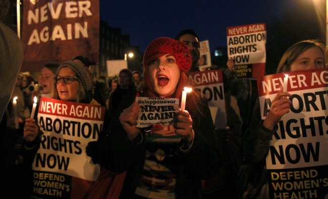 Demonstrators hold placards and candels in memory of Indian Savita Halappanavar....