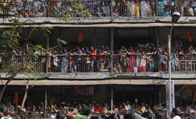 Supporters watch the funeral procession of Shiv Sena party chief Bal Thackeray from a residential...