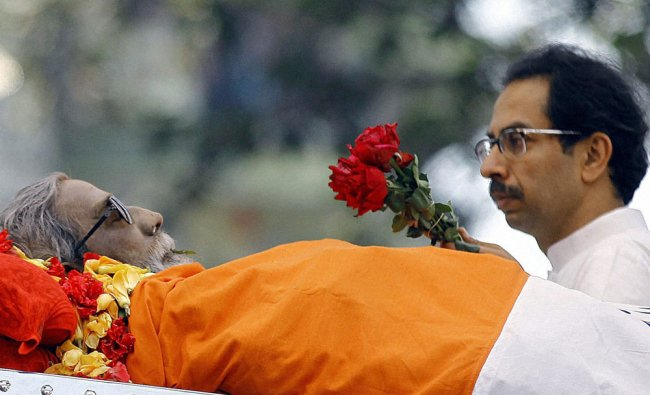 Uddhav Thackeray, son of Bal Thackeray carries flowers past his body during his funeral in Mumbai.