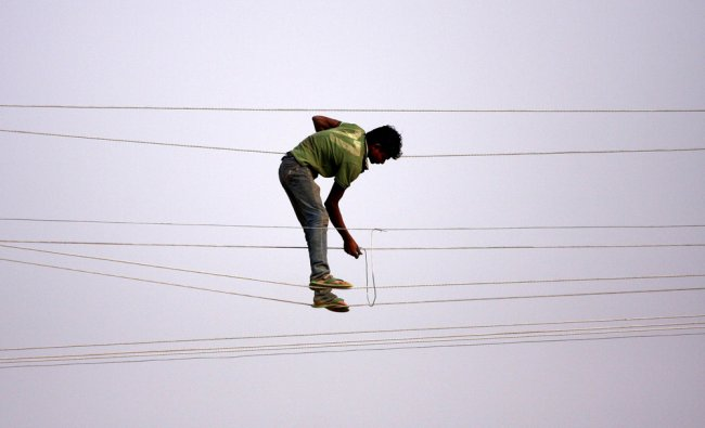 A power department worker make adjustments to electrical power lines