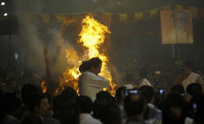 Uddhav Thackeray, center, performs rituals during the cremation of Bal Thackeray
