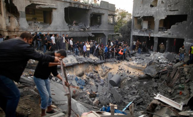 Palestinians gather around a destroyed house after an Israeli air strike in Gaza City