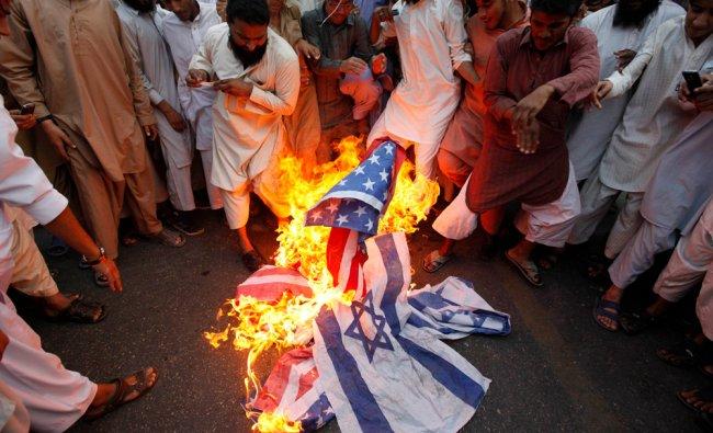 Jamaat-ud-Dawa Islamic organization burn U.S. and Israeli flags during a stir