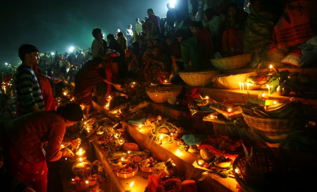 Hindu devotees prepare to offer prayers to the Sun god during the Hindu religious festival ...