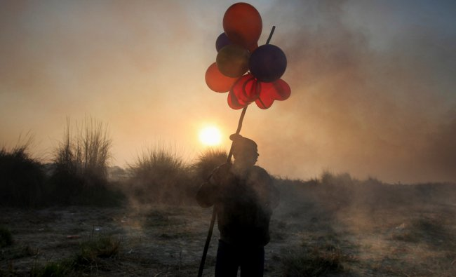 A balloon seller waits for customers on the banks of the Yamuna River during the final day...