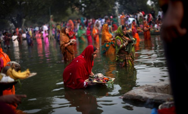 Indian Hindu women devotees offer prayers to Sun God while standing in a water body on the occasion