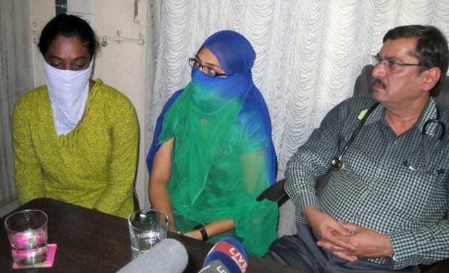 Women arrested for their Facebook posts, Shaheen Dhada, center, and Renu Srinivas, both faces...