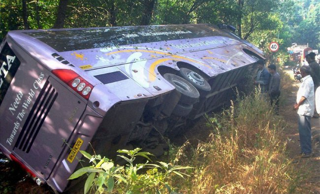 People looking at the ill-fated bus that plunged into a ravine near Chiplun in Ratnagiri...