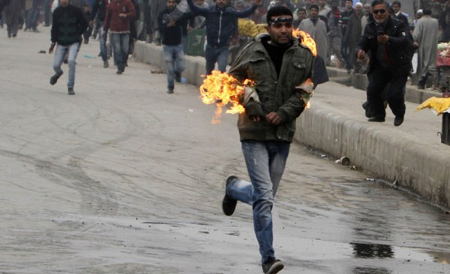 Shia mourner runs after setting his hand on fire during a clash with police in Srinagar on...