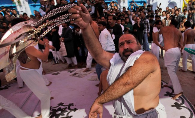 An Indian Shiite Muslim flagellates himself during a procession to mark Muharram in Amroha...