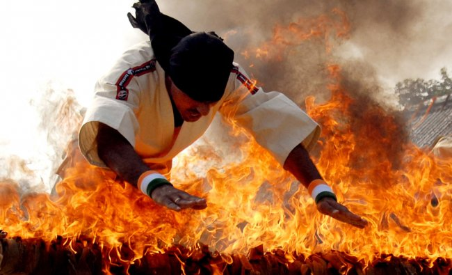 A policeman form CRPF jumps over a burning bar during a passing out ceremony in Jalandhar...
