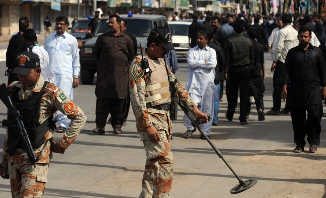 A Pakistani paramilitary soldier uses a metal detector along the roadside...