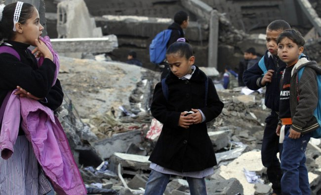 Palestinians school children are seen standing on the rubble of a destroyed building...