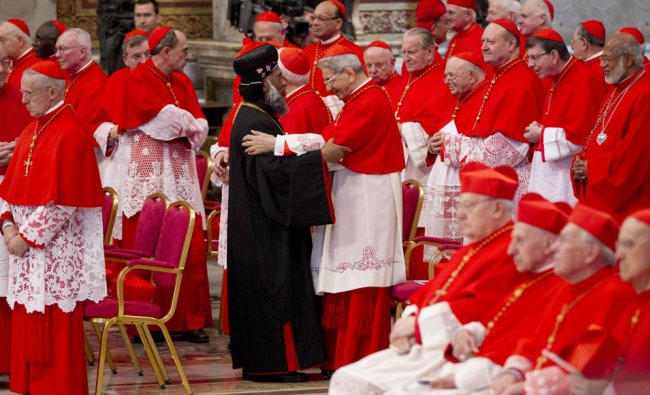 Newly elected Cardinal Baselios Cleemis Thottunkal of India, at center wearing a black suit, is...
