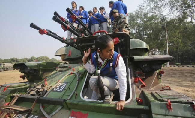 A schoolgirl tries to climb out of a Schilka tank as others stand on it during an exhibition...