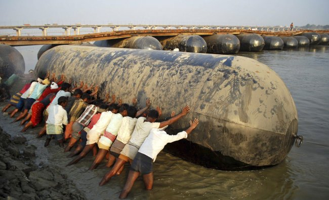 Labourers push a giant barrel for constructing a pontoon bridge over the River Ganges in...