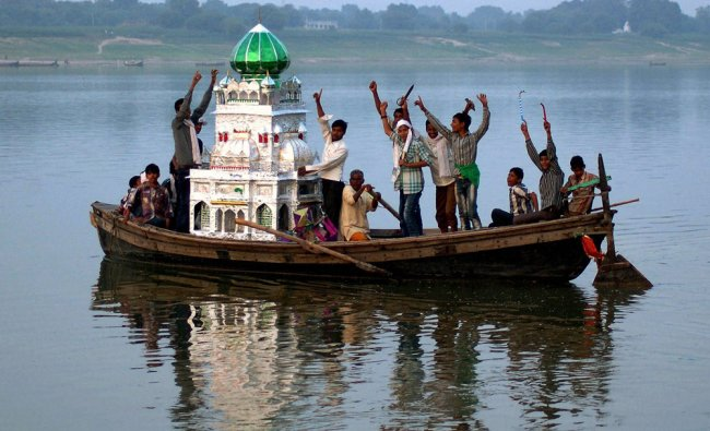 Devotees carry Taziya on a boat in river Ganga after Muharram procession in Mirzapur...