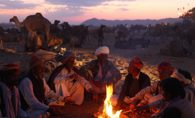 Camel herds men warm themselves on a fire at the annual Pushkar fair in Rajasthan...