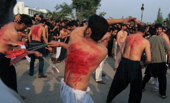 A Pakistani Shi\'ite Muslim man flagellates himself during a Muharram procession ahead of Ashura....
