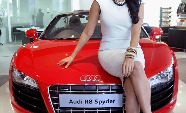Actress Neha Dhupia poses with an Audi R8 Spyder during the launch of its showroom in Ahmedabad
