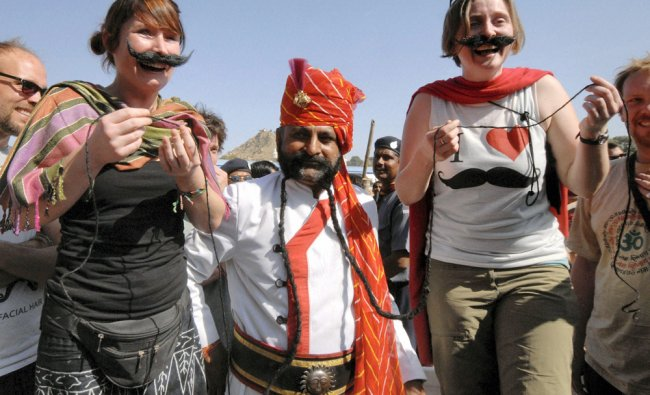 Foreign tourists enjoy a moustache competition at the annual Pushkar fair in Rajasthan on Monday.
