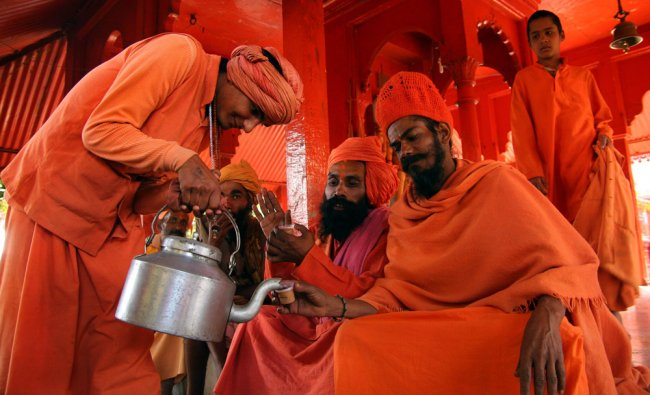 A member of Juna Akhara serves tea after the Bhumi Puja (foundation ceremony), prayer for earth...