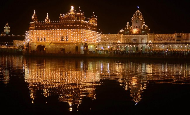 Indian Sikh devotees pay their respects at the illuminated Sikhism\'s holiest shrine Golden Temple...