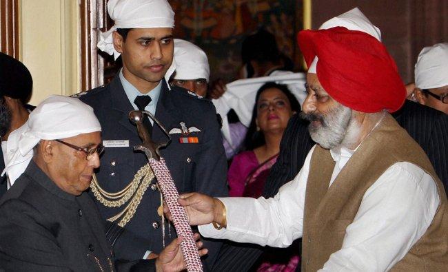 President Pranab Mukherjee receives a sword by a Sikh leader during a Gurbani Recital on the...