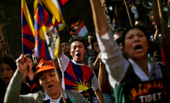 Exiled Tibetans shout slogans during a protest rally to express solidarity with Tibetans...