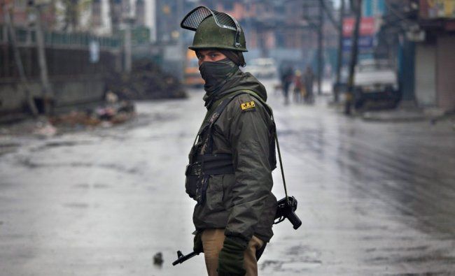 A paramilitary soldier stands guard at a temporary check point during curfew in Srinagar...