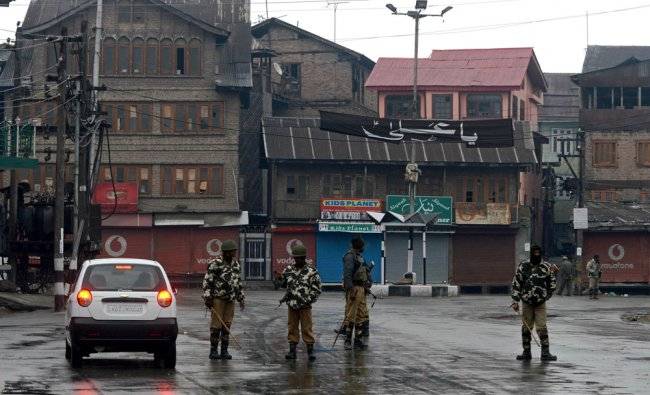 Para-military soldiers stand alert in a heavy downpour during a indefinite curfew in Srinagar...