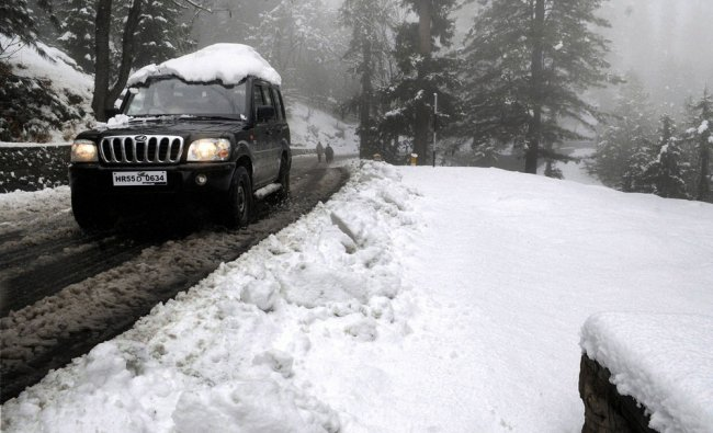 A tourist vehicle moves on a snow covered road near world famous Ski resort of Gulmarg after...