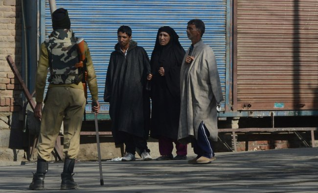 Paramilitary soldier stops a Kashmiri family as they walk along a street during curfew in Srinagar..