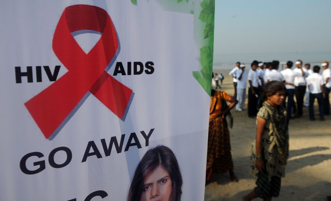 People walk past a banner with an AIDS awareness message at a rally on World AIDS Day