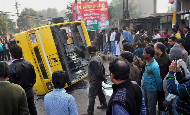 People looking at the school bus that was hit by government bus while carrying students at Civil...