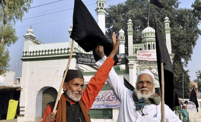 Muslims shout slogans and hold black flags during a protest on the 20th anniversary of the Babri...