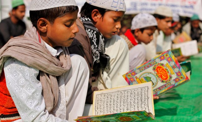 Muslims read holy book as they offer prayers on the 20th anniversary of the Babri mosque demolition