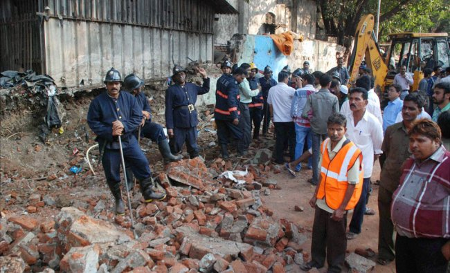 Fireman carrying out rescue work after the collapse of a wall of Byculla Station in Mumbai...