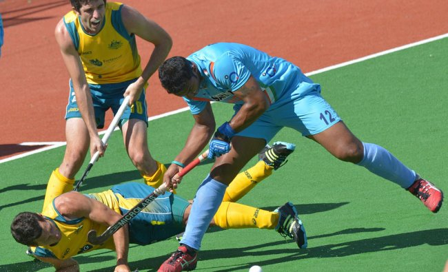 Jamie Dwyer of Australia (L) is falls next to Raghunath Vr of India (R) in the second semi final...