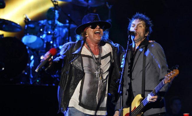 Axl Rose, left, lead vocalist of Guns N\' Roses performs with bass guitarist Tommy Stinson during...