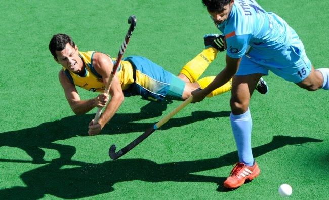 Luke Dwyer of Australia takes a strike on goal under pressure from Uthappa SK of India ...