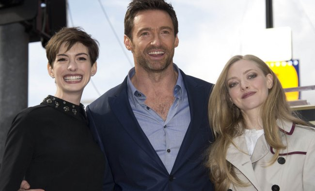 Actor Hugh Jackman poses with his actresses Anne Hathaway (L) and Amanda Seyfried at his star on...