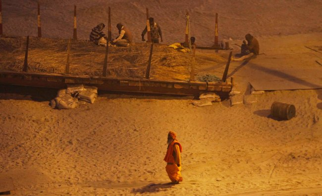 A sadhu, or Hindu holy man, walks as Indian laborers work for the upcoming one-month-long...