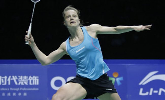 Juliane Schenk of Germany returns a shot against Saina Nehwal of India in the womens singles...