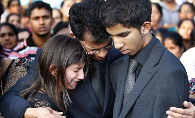 Jacintha Saldanha\'s widower Ben Barboza (C) and her children Lisha (L) and Junal mourn during her...