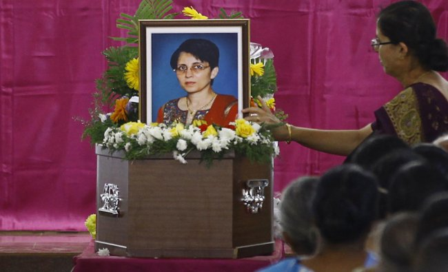 A woman puts flowers on Jacintha Saldanha\'s coffin during her funeral inside a church in Shirva...
