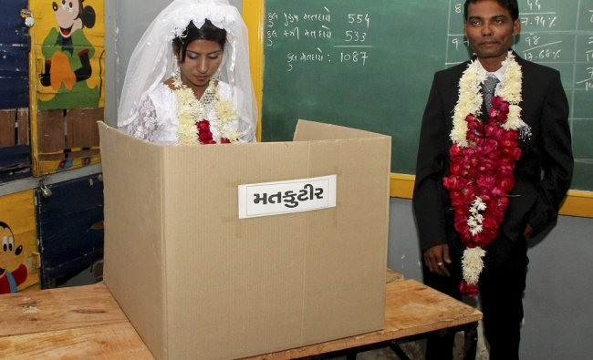 Christina Christian (L), a newly married bride, casts her ballot as her husband Kinjan Tailor...