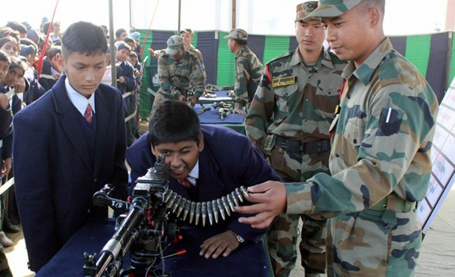Students having a feel of army weapons at an exhibition during the Indian Army Mela at Khasa...