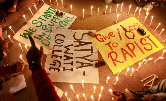 Students light candles at India Gate during a protest against the recent gang rape case in New Delhi